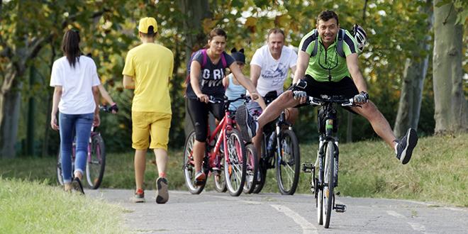 Ljudi šetaju i voze bicikle u gradu