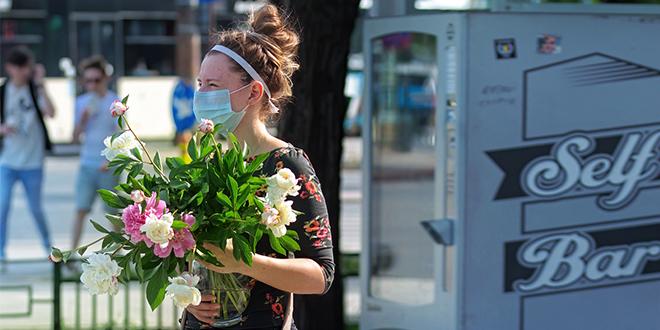 Девојка носи заштитну маску и носи цвеће у рукама