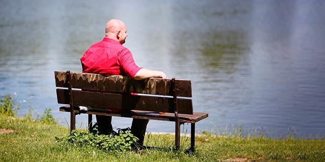 Muškarac sedi na klupi i odmara