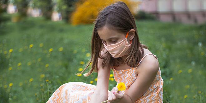 Девојчица бере цвеће са заштитном маском
