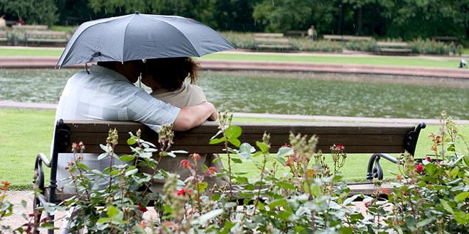 Брачни пар седи на клупи и држи кишобран