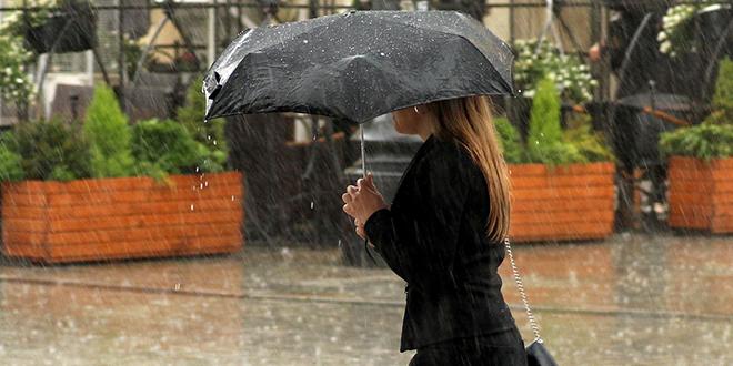 Kiša, žena nosi kišobran