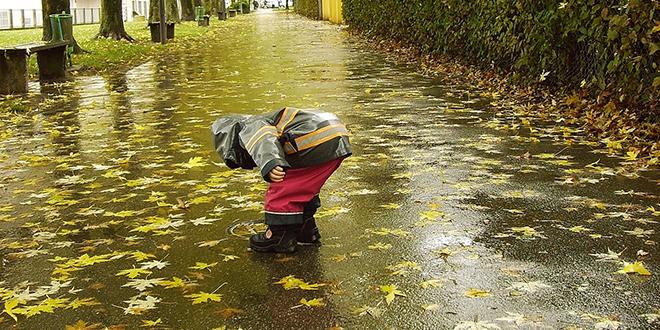 Jesen, kiša, dete skuplja opalo lišće