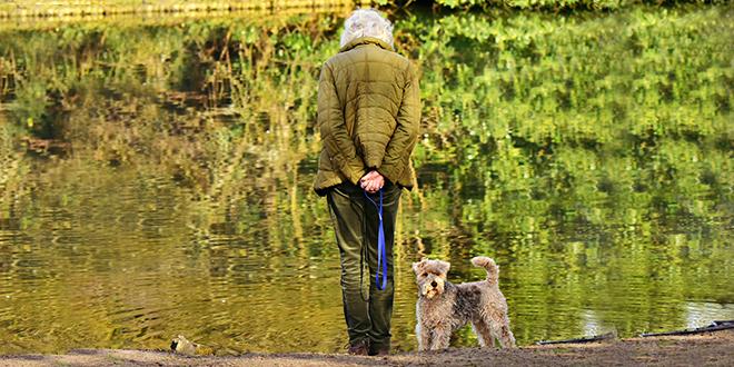 Starija žena stoji pored jezera sa svojim psom
