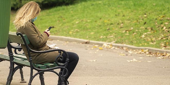 Žena sa telefonom u rukama sedi na klupi u parku